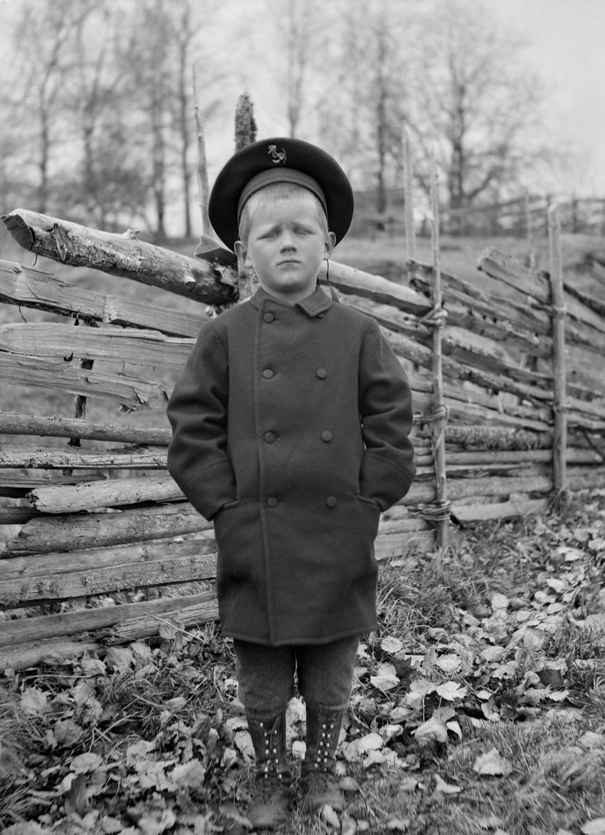 Uno Hallin poserar intill en gärdesgård rimligtvis vid hemmet Middagsfisket i Sankt Anna socken. Son till Karl Johan Hallin och fotograf Durlings syster, Hedvig Maria Bertha Durling.