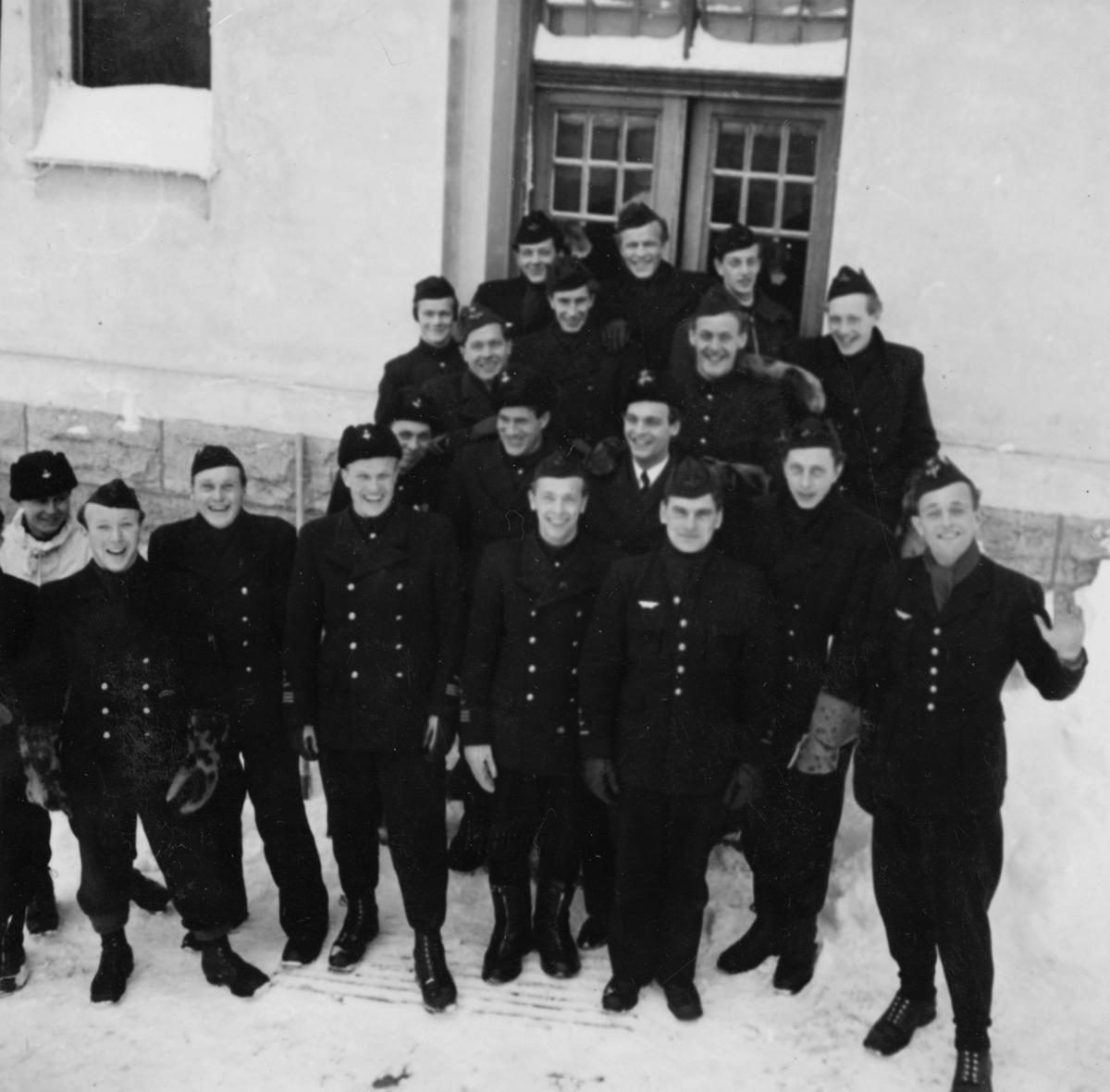 Gruppfoto av mekaniker och flygförare från F 14 före den planerade flygningen Halmstad-Kiruna i februari 1946. 19 män samlade framför hus. Flygningen slutade i nödlandning i Härnösandstrakten den 10 februari 1946.