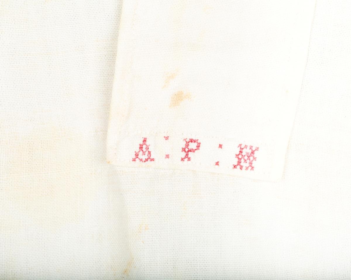 Hverdagsskjorte. Splitt og stolpe foran. På stolpen korsstingsmonogram A P H.  Sidesplitter, Ny skjortekrage i tynnere stoff - erstatter trolig gammel linning. Lange ermer. Forsterket skulderparti Toskaft bomullsstoff.. Maskinsøm. Håndsyddr knapphull . Nyere plastknapper på armlinning, kile under armhulen. Ermet rynket til armlinning