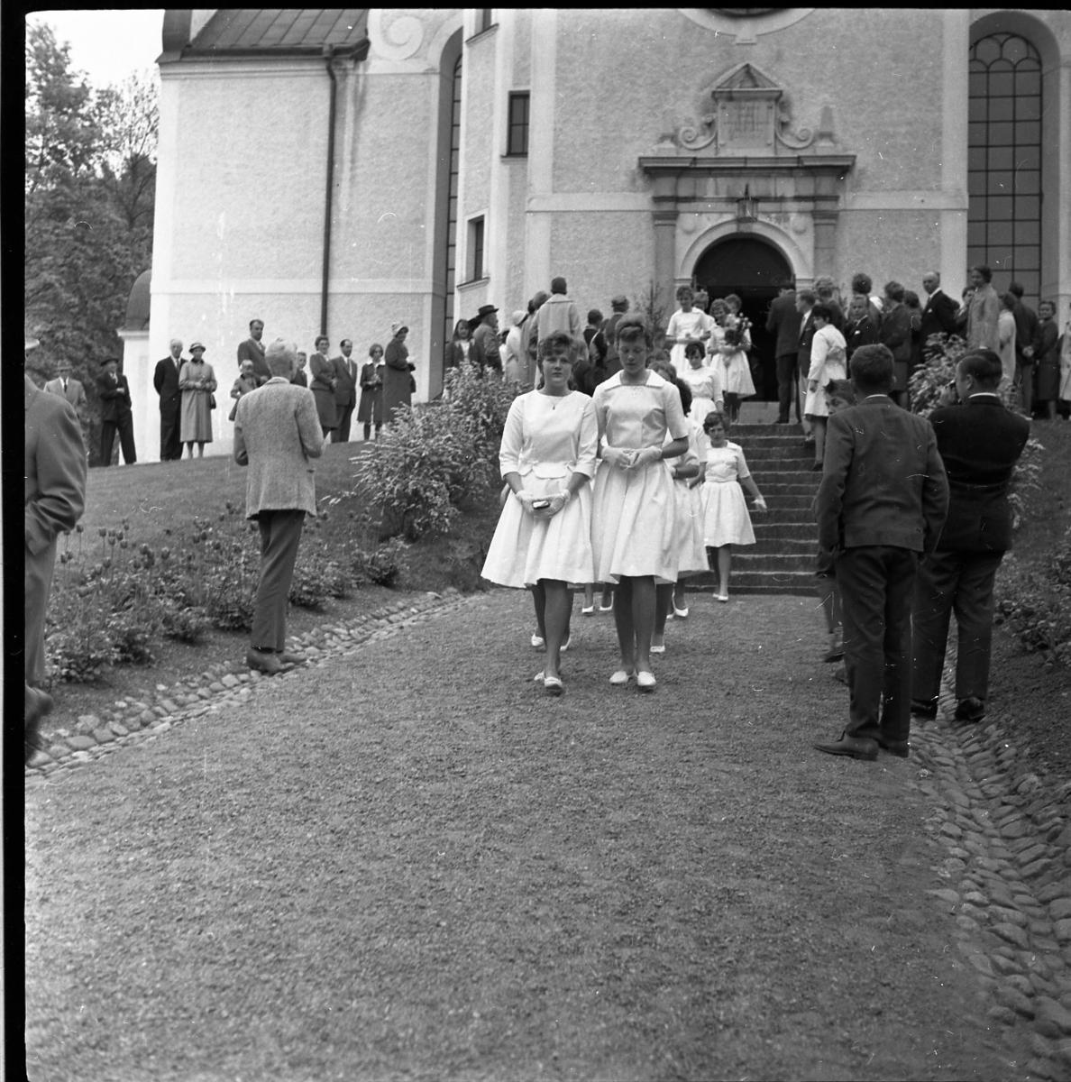Kvinnliga konfirmander på väg ut ur Gränna kyrka. Deras väg kantas av barn och vuxna.