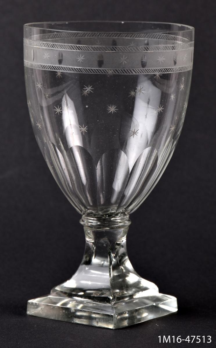 Ölglas, med fyrsidig fot, slipat och etsat, upptill en bård med stjärnor och små ovaler, längre ned stjärnor.