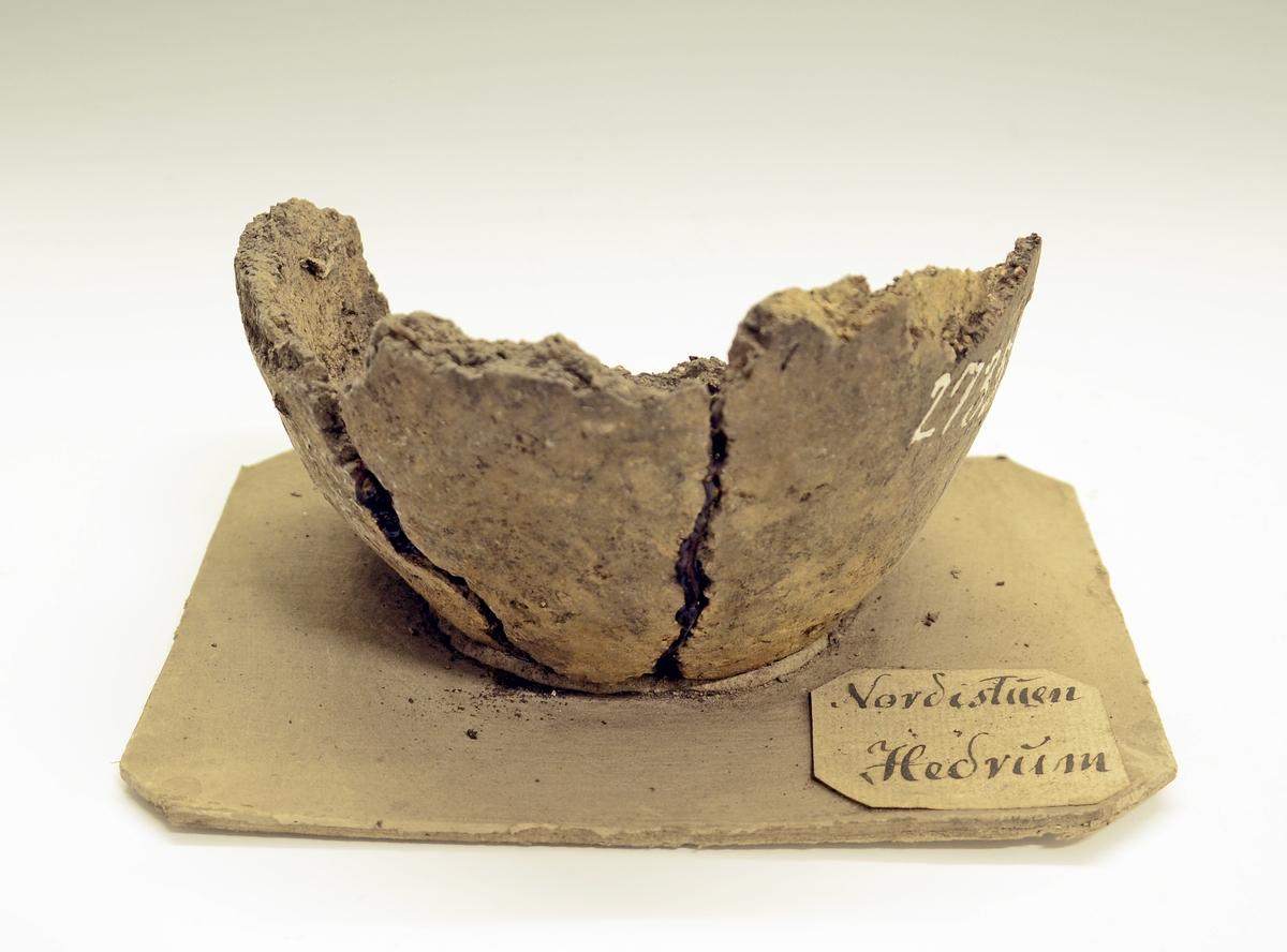 Fra protokollen (J. S. Munch, 1952):  Leirkar i fragmenter, bare bunnen og noe av siden bevart, hele overdelen med randen  mangler. Godset er grovt, grålig av farge, noe avglattet på oversiden. Formen kan komme opp imot Rygh 354.   Disse saker (SM.2733-2737) ble funnet i en stor rund gravhaug 24 fot i tverrmål og 4 fot høy. I haugen, som tidligere var noe forstyrret, var det 4 store brannsteder. Oldsakene forteller også at her har vært flere graver, idet den ovale spennen helst bør dateres til yngre del av merovingertiden mens leirkarene er eldre, uten at de med sikkerhet kan dateres.