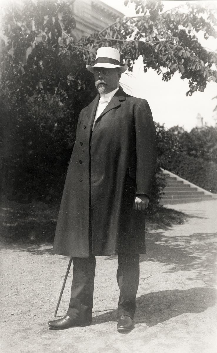 Foto av en medelålders man med pipskägg och glasögon, klädd i rock och panamahatt m.m. Han står på skolgården utanför Växjö läroverk.