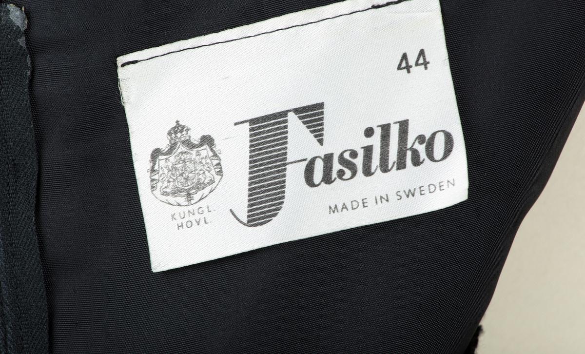 """Selskapskjole (smoking) i ull og silke, sort, foret med vlisiline. Skåret i 7 bredder, innsvinget i livet, 2 sidesnitt. Ermeløs. Båtformet utringing. Bærestykke i forsilke. Kjolestoff lagt som løs kappe over brystpartiet. Fabrikkmerke: """"Fasilko/ made in Sweden"""". Str.44.  Se foto Fhm.10094.c Tilstand: God  Giver:     Astri Breder Berg f.ca.1942 og Jens Christian Berg, Oppegård. Bruker:   Ingeborg Berg f.18.10.1897, mor til Jens Berg, tidligere eier og bruker.                Kjolen brukt i bryllupet til giverne i Riis kirke 1963. Ant. også brukt i Marialosjen. Ref.FHM.10094.A-C."""