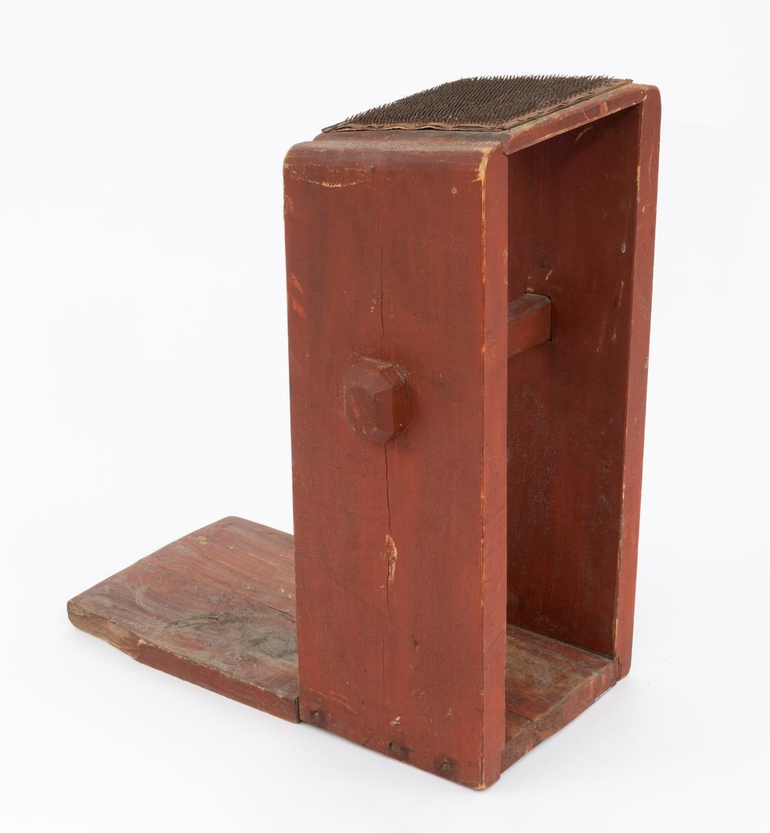 """Dette objektet er del av en gruppering som består av to kardekrakker og en håndkarde som er brukt til å bearbeide ull, slik at den blir klar til å spinnes til garn. Dette skjemaet omhandler den ene kardekrakken (krakkarden). Kardene av denne type er brukt til første gangs karding av ull. Ulla som behandles ligger an på kardekrakken og blir beharbeidet med en håndkarde.  Kardekrakken, krakkarden, består av en kasselignende konstruksjon som er montert vertkalt til en treplate (fot). Kassas topp består av en plate som er trukket med et tilnærmet kvadratisk lærstykke. Fra lærstykket stikker det opp små bøyde nåler av jern. (Ulla som skal behandles legges an på denne """"nåleputa""""). Kassas sider er festet med smidde spiker til foten. Mellom kasseveggene, er det strukket en stolpe, strekkfisk. Det er gjennomgående hull i begge kassevegger som stolpen er strukket gjennom. Stolpen er låst med en kile på ene siden."""