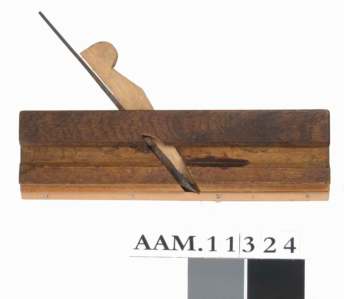 Smal høvel med tretrinns såle. Ytterst er en smal list av ubehandlet tre som er stiftet på med fire stifter (nytt). Øvre del av samme side har pålimt  et stykke mørk eik. Ny kile.