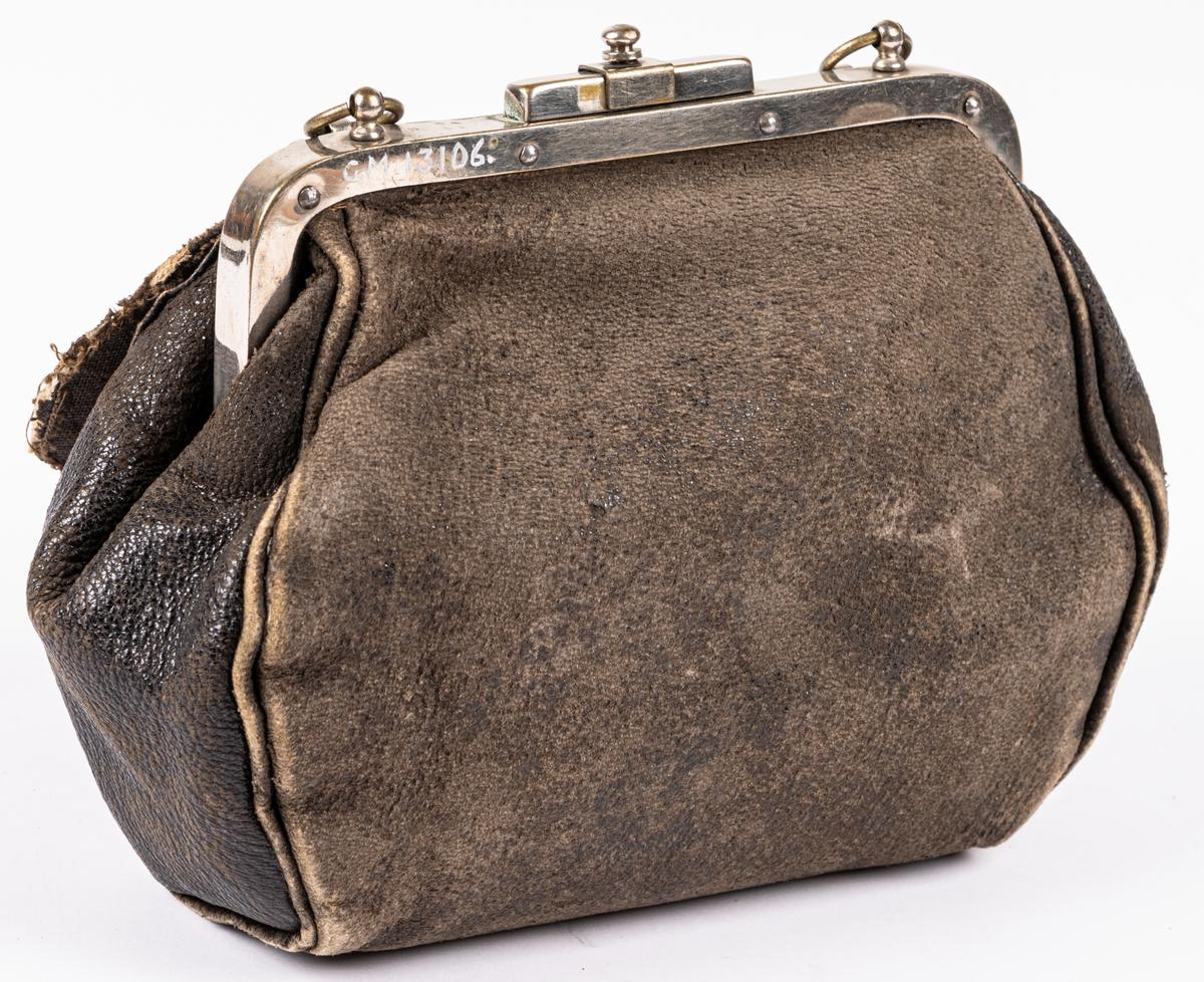 Väska av läder med två knäppen, bygel av vitmetall, handtag av läder, svart.