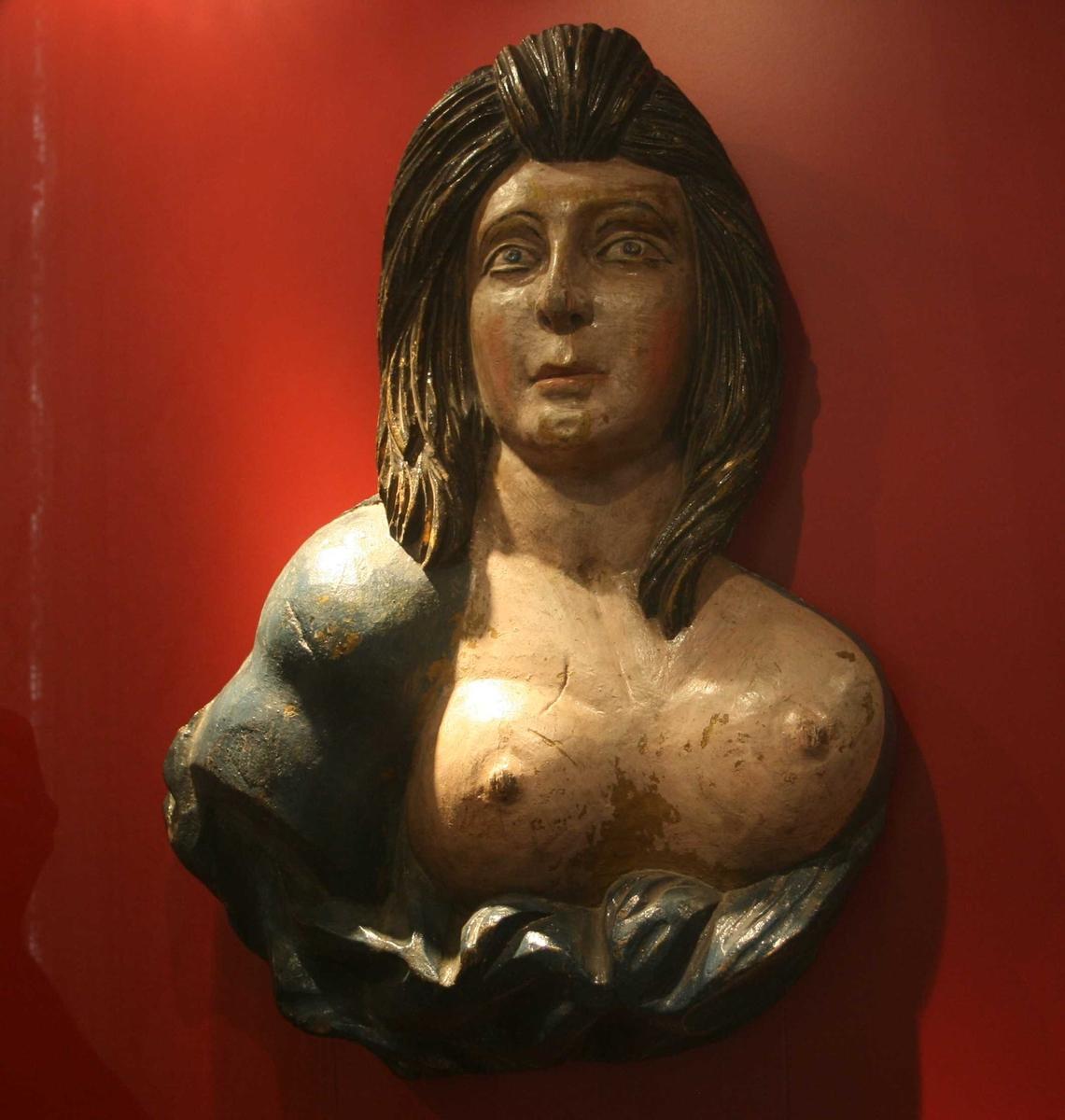Kvinne med utslått, sort hår  til skuldrene, nakent bryst, draperier under  brystet. Draperi og h. skulder blåmalt.