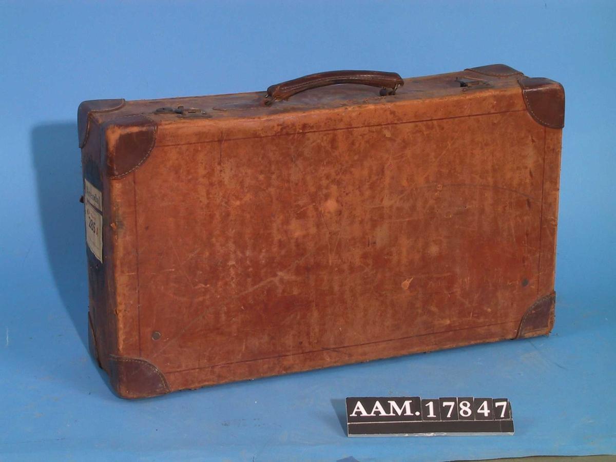 Koffert.  Brunt skinn, innvendig foret med lyst gulbrunt lerret.  Rektangulær koffert med skinnhjørner, messing i lås.  Noe oppskrapet, etikett for jernbane Oslo til Arendal.