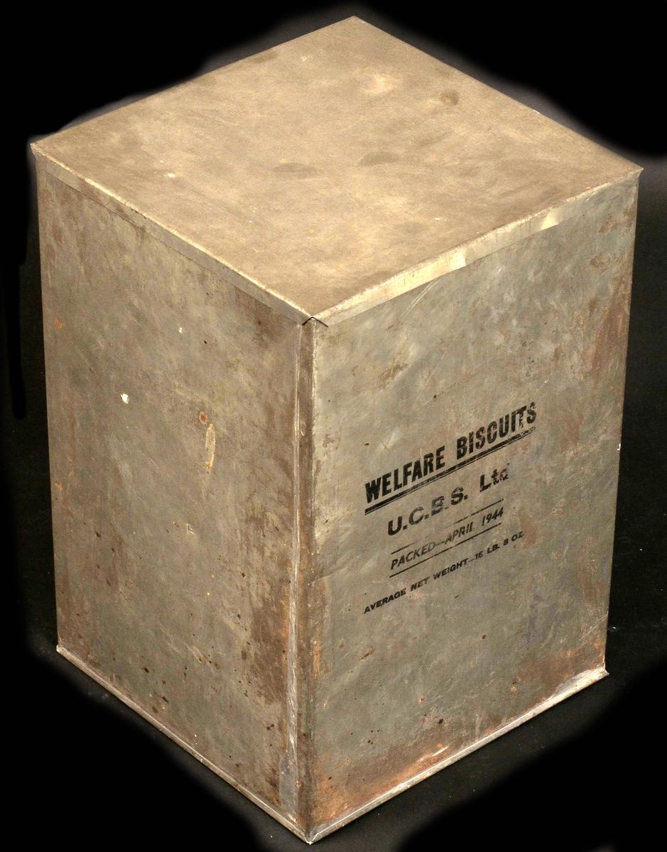 Kubeformet boks. Laget av valset jernblikkplate, loddet sammen, malt tekst etter sjablong.
