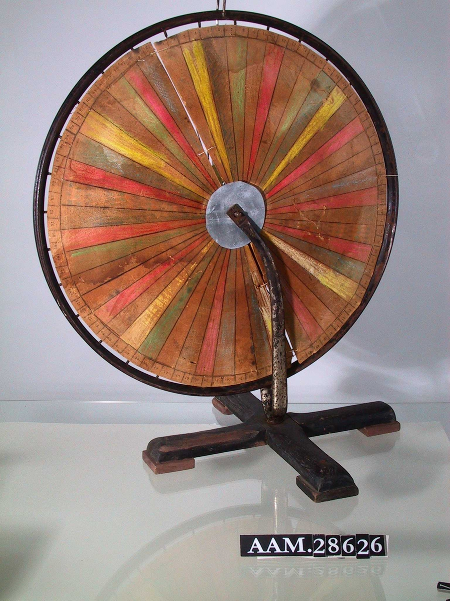 Laget av et sykkelhjul med påmontert en sirkelrund pappskive; hjulet står i en sykkelgaffel montert på en fot som likner en juletrefot. Pappskive i sektorer i ulike farger. Pappskiven er bundet til sykkeleikene med tråd.
