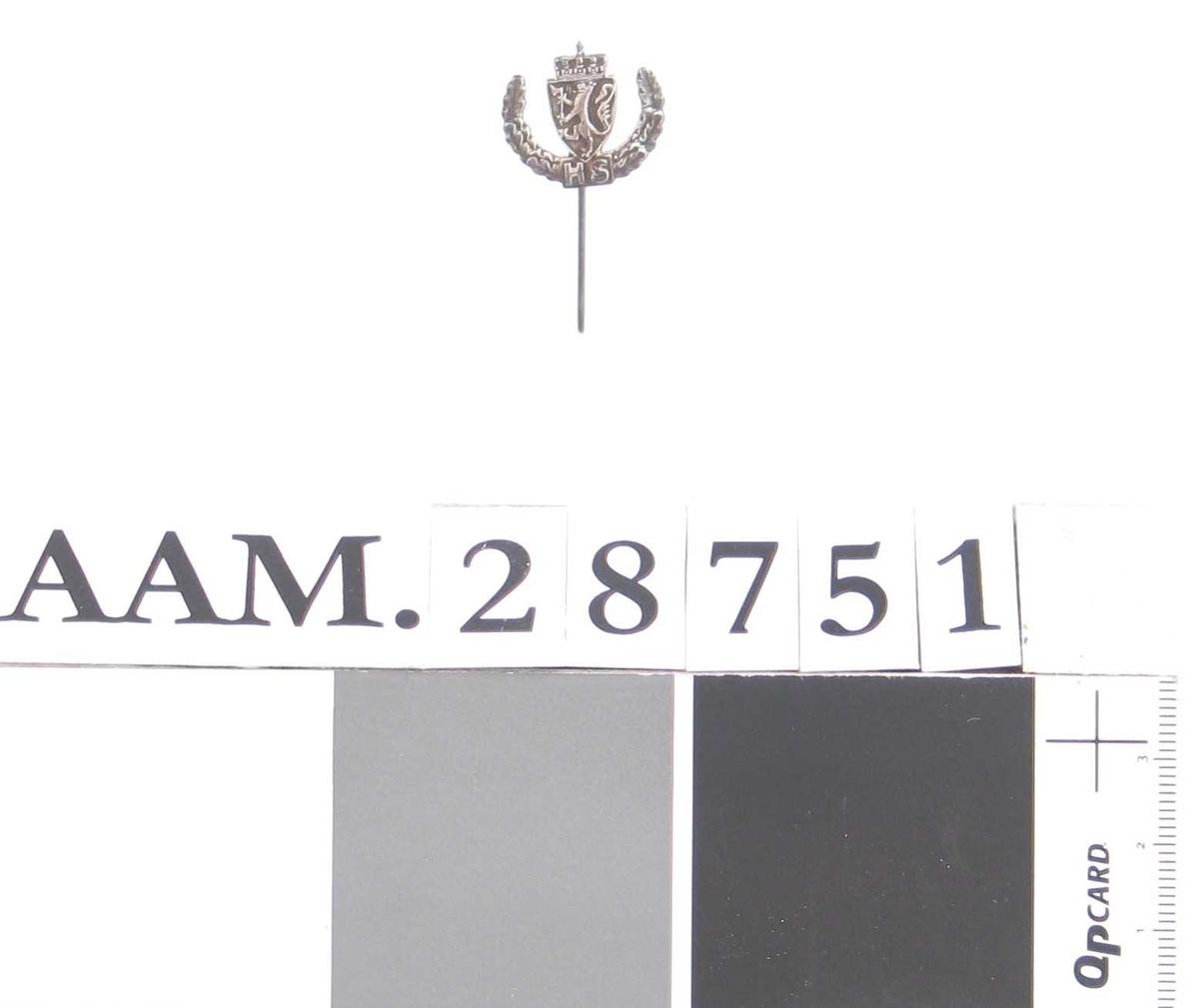 Krans av eikeløv, e.l. riksvåpen m. løve. bokstavene HS = Hjemmestyrkene