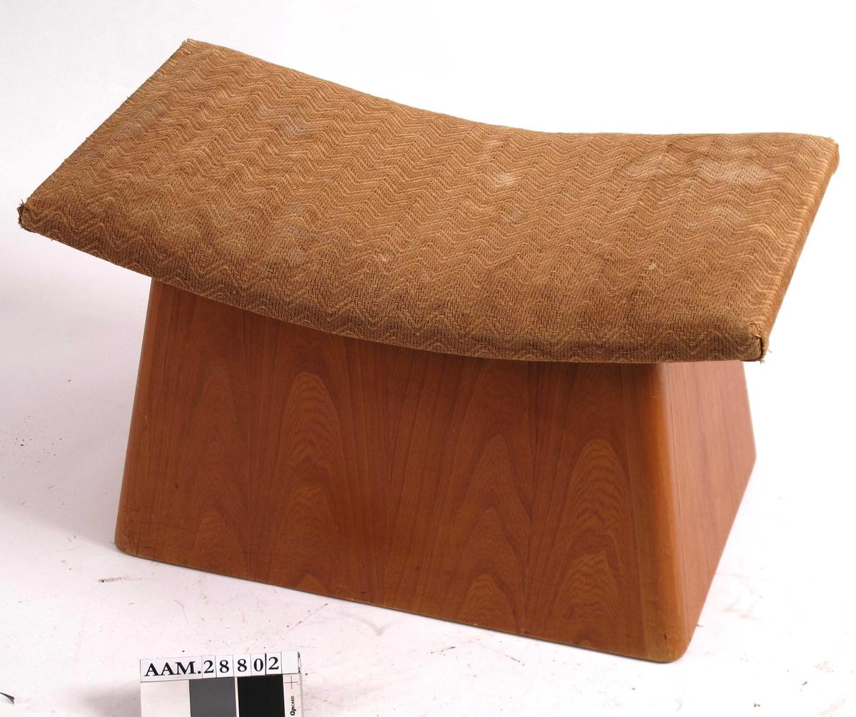 Kasse av finert møbelplate (tykk kryssfiner), med utoverskrånende sider, påmontert hengslet lokk, bueformet som et sete, trukket med møbelstoff vevd av papir eller cellull. Kassen har buede hjørner, med staver som sideplatene er slisset inn i. Beiset (?) og lakkert overflate. Tilstand: Ved innkomst var lokket løst, og ble fastskrudd. Fineren noe fliset langs øvre kant.