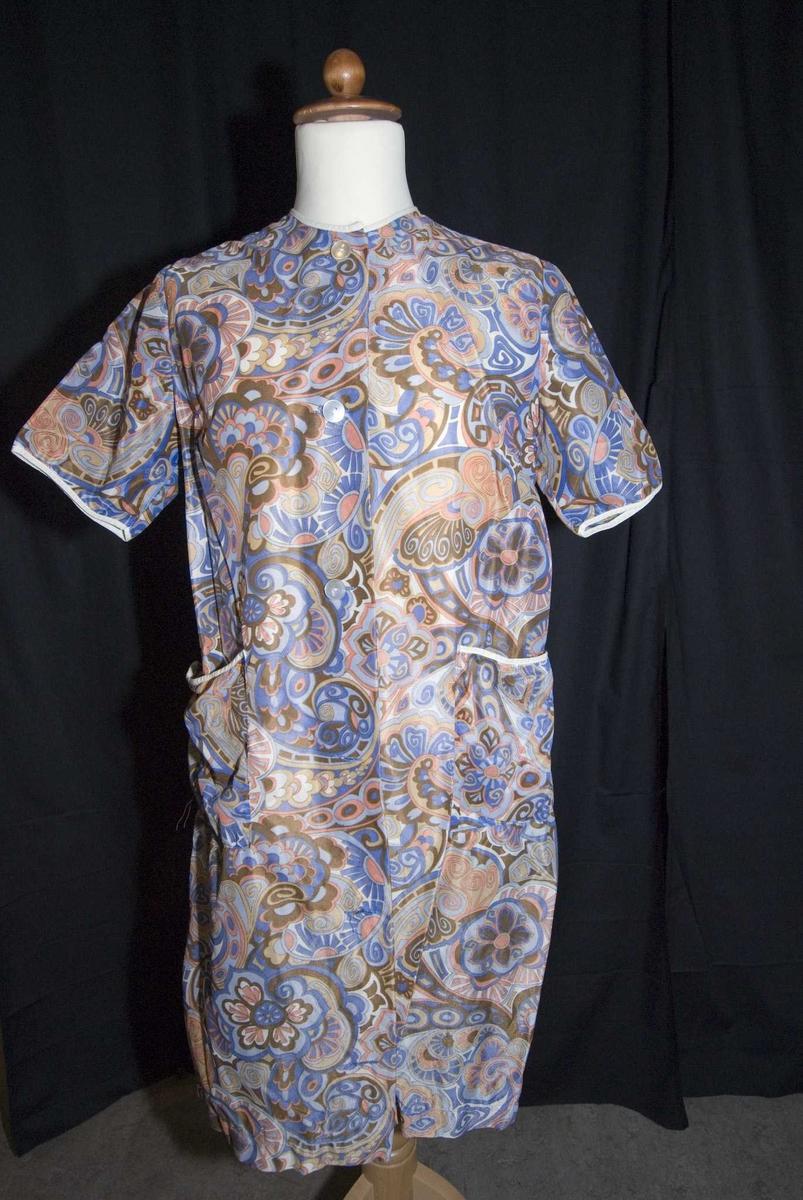 Mønstrert forkle med korte ermer, to små lommer foran, kneppet åpning foran, kantet med hvite skråbånd rundt halsen, ermene og på lommene.