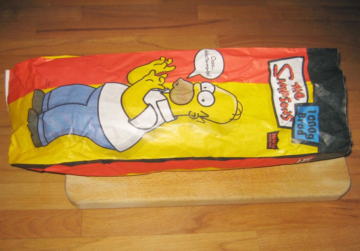 """Forsiden: Motiv er tegneseriefiguren Homer Simpson fra the Simpsons. Han står og sier (i en tegneserieboble) """"Oooo...delecta-ma-ble! Baksiden: Hele Simpson-familien + hund og katt."""