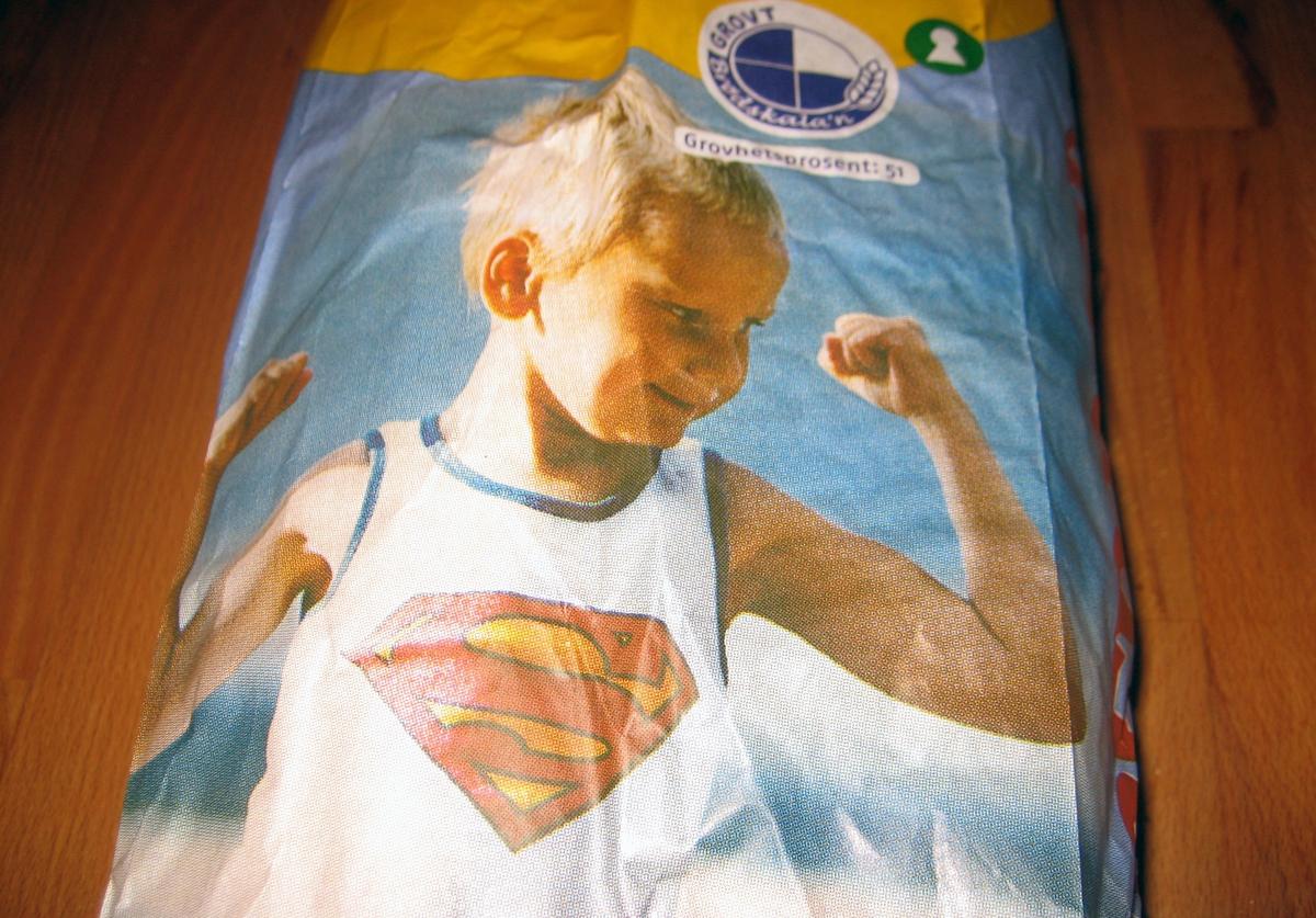 Motivet på posen er en liten gutt som har på seg en singlet med supermannslogo. gutten har hevete armer med knyttede never slik som en bodybuilder.
