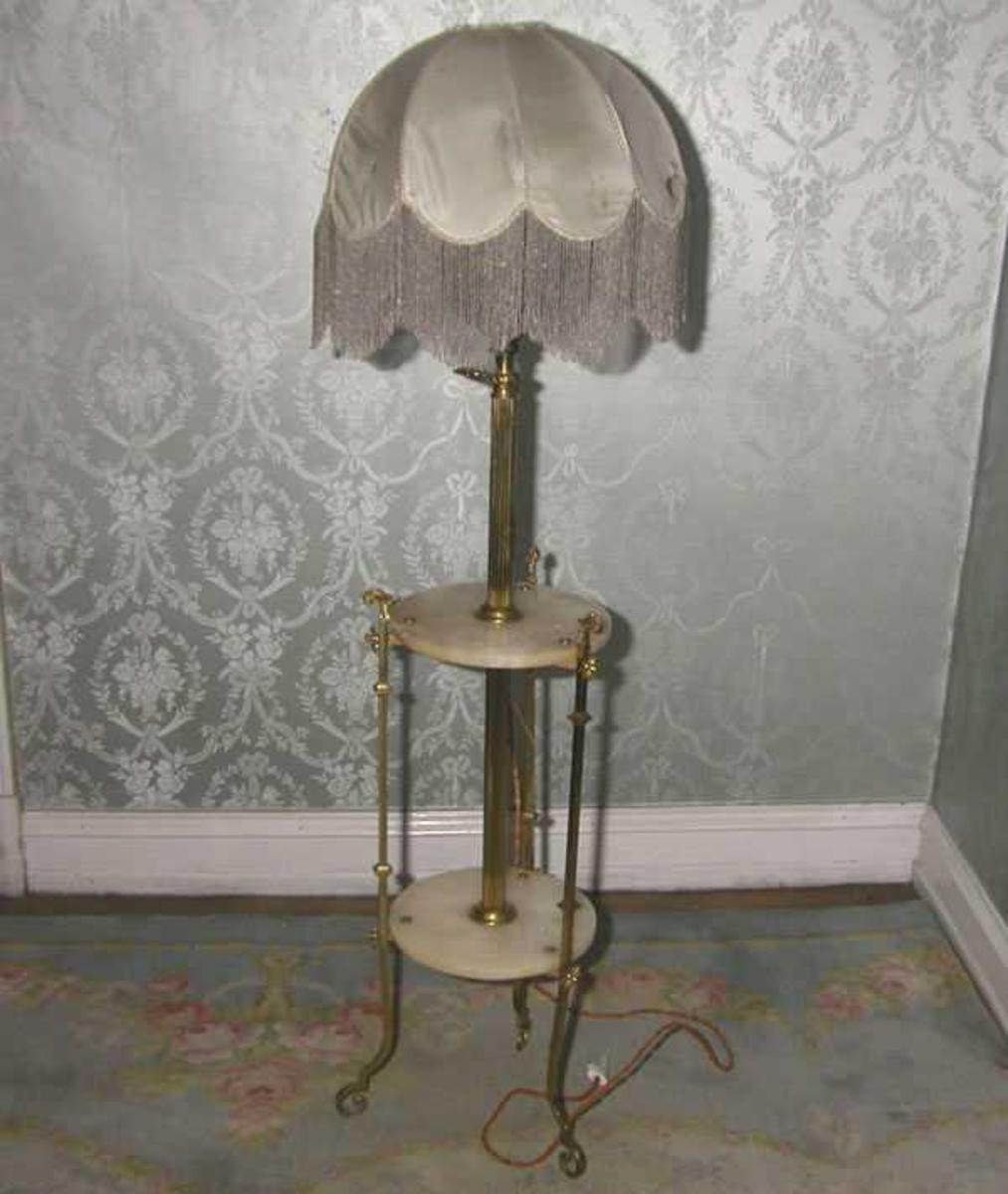 """a) Stålampe i gult metall med onyxplater. runde plater festet til lampefoten med blomsterformede metallfester. 3 støtteføtter i gult metall med rokokkomønster. b) Hvit silkeskjerm, delt i 10 felter med grå perlerysjer i tunger. Oprinnelig parafinlampe med skål under pærefeste, nå; elektrisk med pære.  """"En messing staalampe."""" Inventarliste fra Gustav Amundsen 1934."""