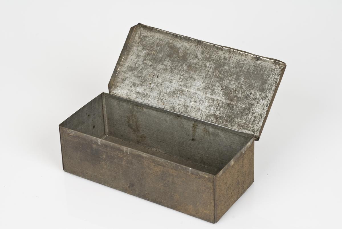 Rektangulær metallboks med lokk. Boksen er tom.