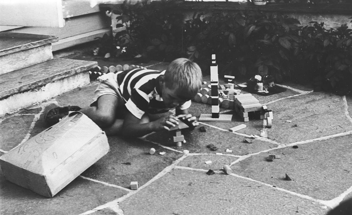 Gutt ligger på trappa og bygger klosser (lego).