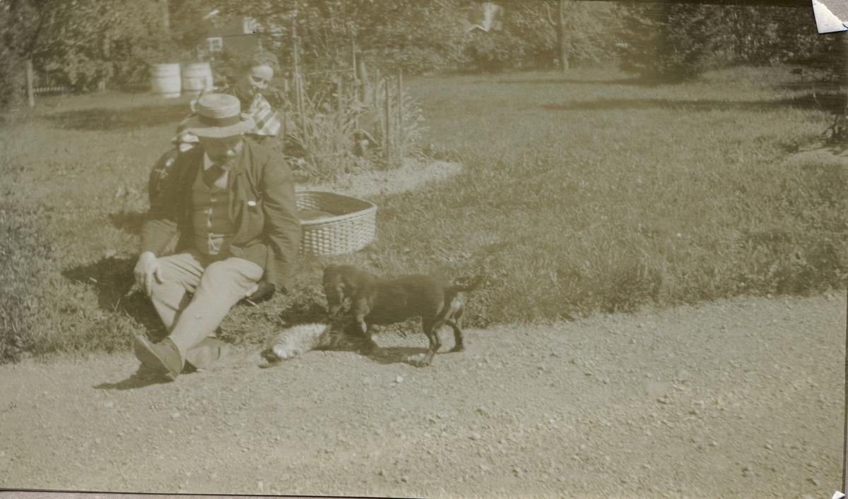 Gabriel Kielland Hauge og en dame i hagen med en katt og en hund.