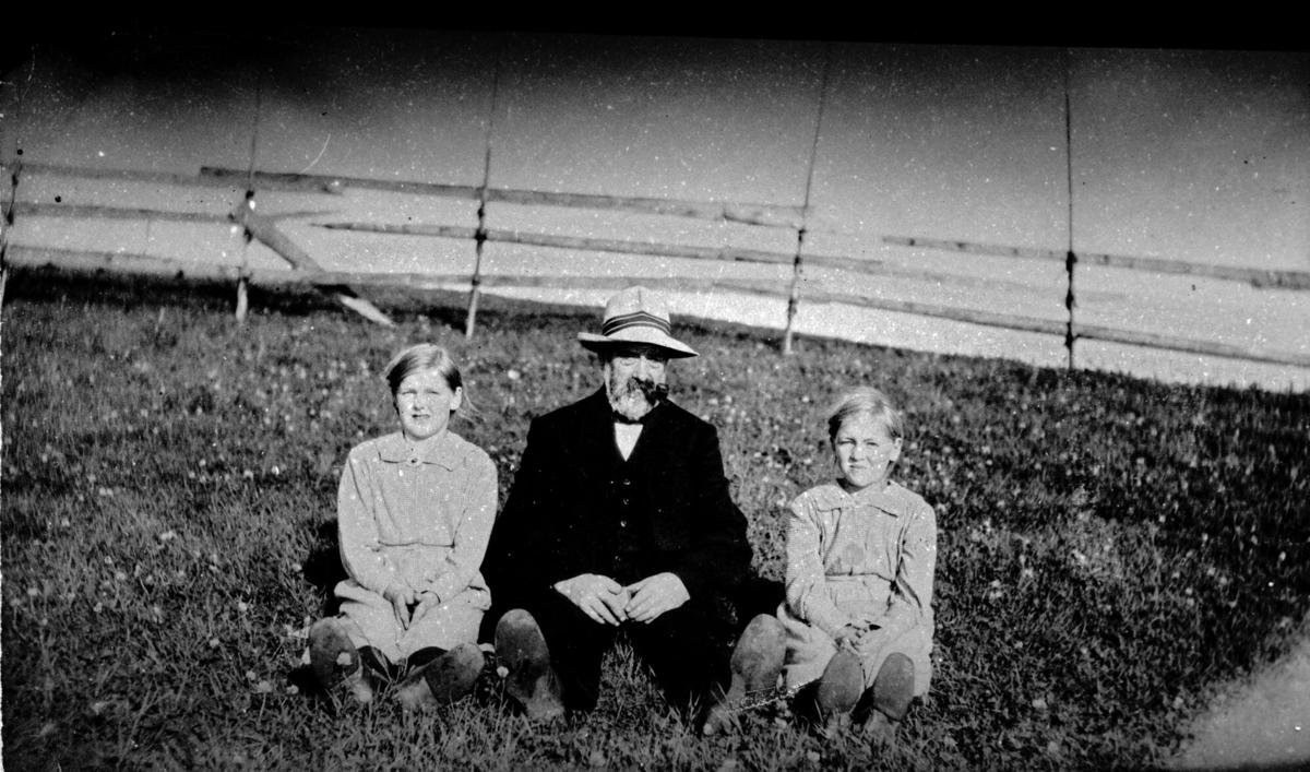 Gammel mann og to jenter sitter i gresset.