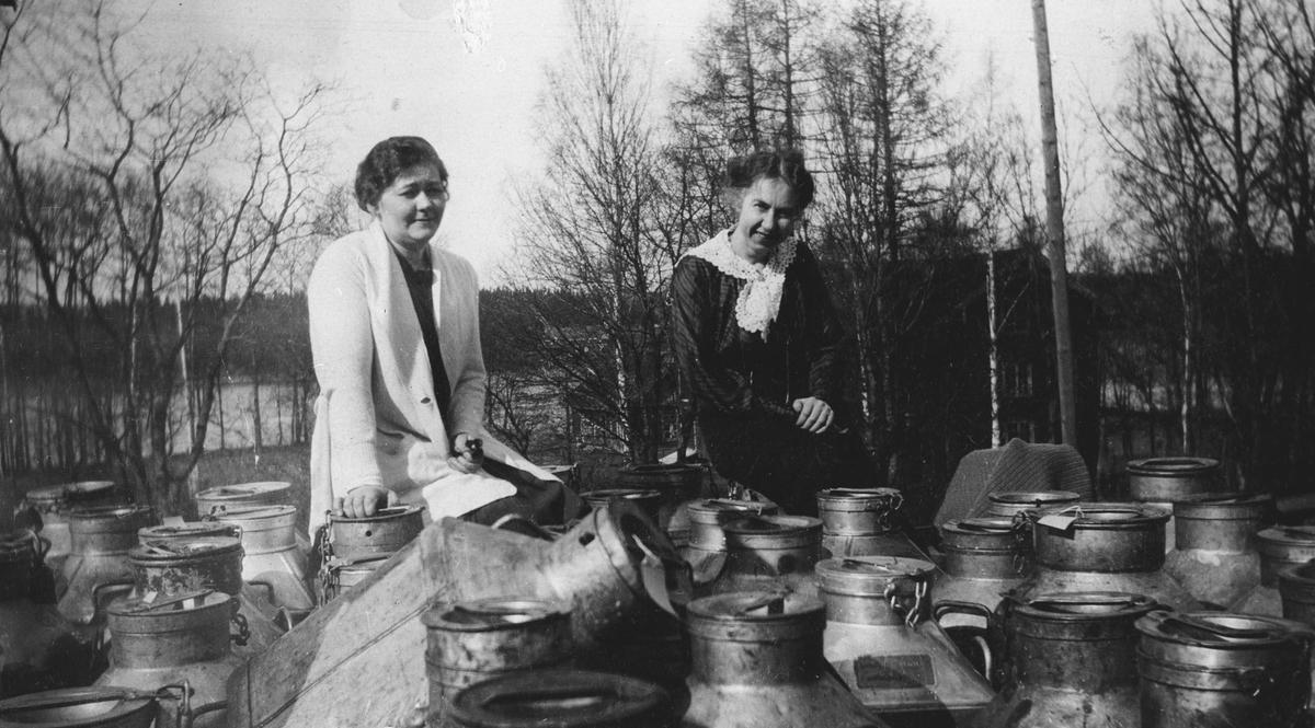 To kvinner med tomme melkespann på perrongen