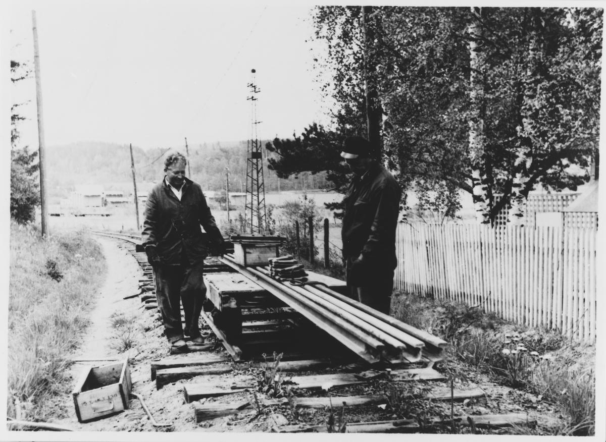 Riving av Urskog-Hølandsbanens spor på Bjørkelangen. Arbeidet utføres med håndkraft, og skinnemateriellet kjøres inn med håndtralle. Hans Bådahl t.v.