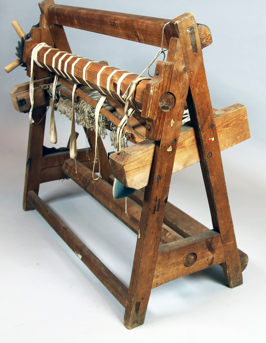 """Vev som står på sidestykker bestående av to bein hver som møtes i toppen og er forbundet med et tverrstykke nede. Dette tverstykket er den nedre bommen festet i. Bommen kan dreies med et dreiehjul som har tannhjul og kan """"låses"""" med en metallsperre som går inn på tannhjulet.  Veven har to bommer og to hovler. Øvre bommen har samme dreie og låsemekanisme."""