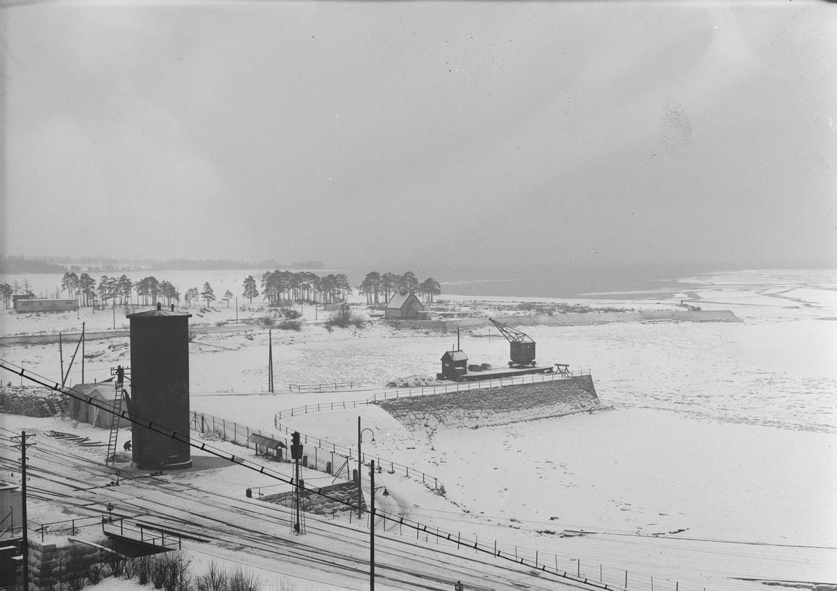 GARVER KIRKEBY, TJUVHOLMEN, HAMAR.  Oversiktsbilder, Tjuvholmen, Vesle-Mjøsa, robåter, vinter, vanntårn ved Hamar jernbanestasjon, Jernbanebrygga, Hamar.