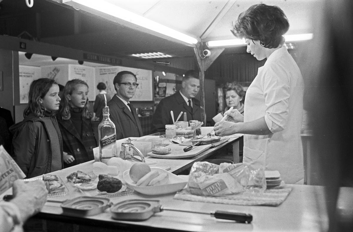 """Serie. Utstillingen """"Vår husholdning"""" på Sjølyst. På den polske standen står en kvinne og demonstrerer mat. Fotografert 20. septermber 1969."""