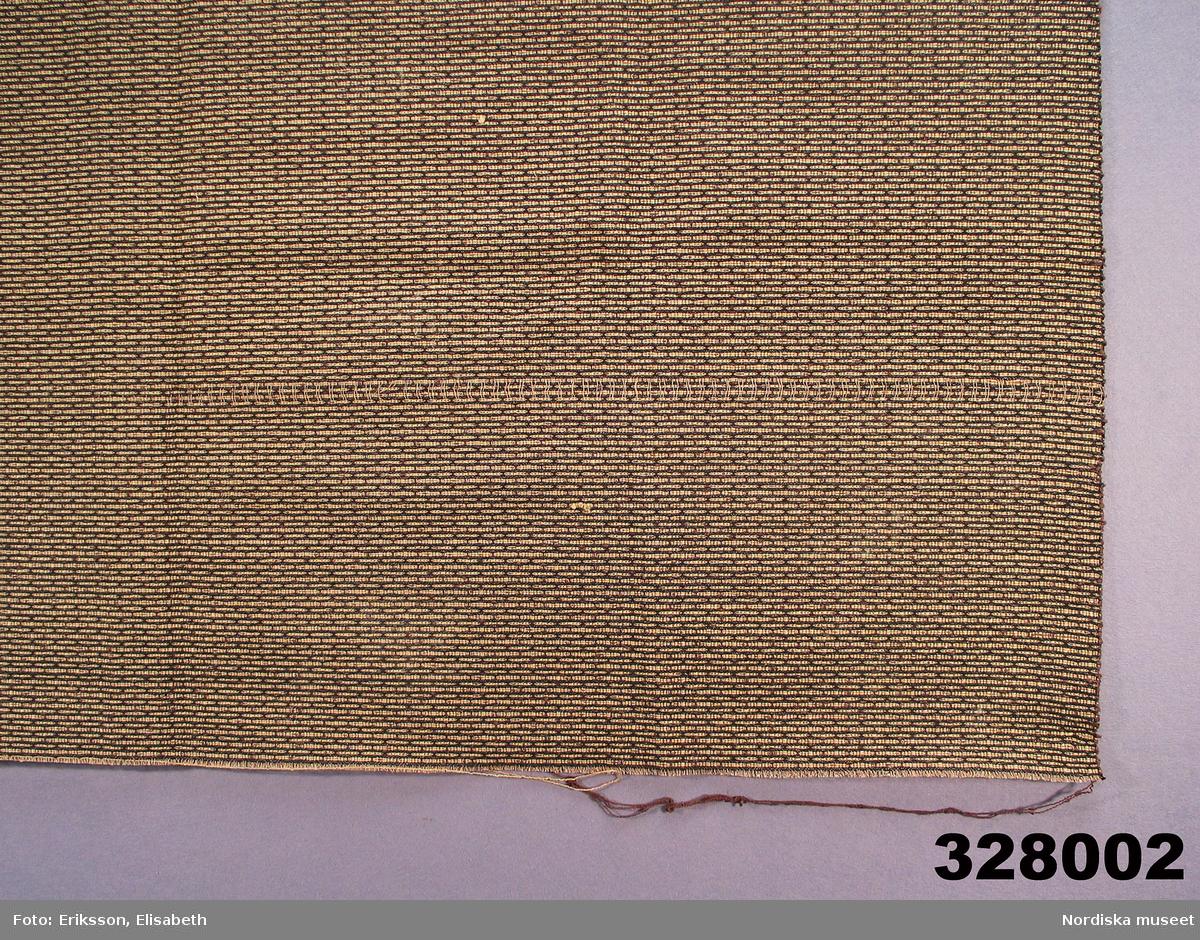 """Varp av tunt beige tvinnat bomullsgarn och på varje cm en effekttråd i ljust konstsilke. Inslag av brunt bomullsbouclègarn och beige cellullgarn som bildar ett randigt prickmönster mot den bruna boucléytan, dessutom ett svart inslag som inte syns på framsidan men framträder på baksidan. Bildar en fast och stadig kvalitet. Användes som överkast och stora dynor till en dyscha i makarna Tamms hem. I samma rum låg flossamattan inv.nr                  och """"Tuppmattan"""" i röllakan inv.nr                    Foton från rummet finns.  Stella Sawers 1878-1968 f. i England, gift 1900 med Percy Tamm 1878 - 1963 född på Fånö i Uppland. Ägde och bodde fastigheten Heleneborgsgatan 4A, Stockholm, ett hus byggt i mitten av 1930-talet. Lägenheten inreddes då av arkitekt Albin Brag. Se även möbler inv.nr 327.952-955, samt foton från hemmet i Arkivet  Berit Eldvik dec-02"""