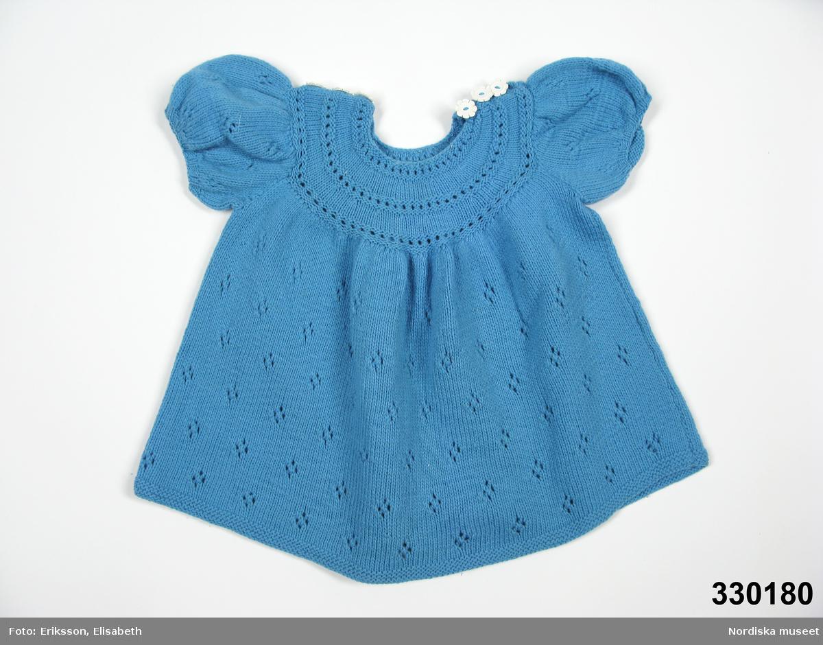 Slätstickad blå klänning med genombrutet mönster, för ca 2-årig flicka. Fram- och bakstycket identiska, hopsydda med sidsömmar. Runt halshål omgärdat av ömsom rätstickade partier, ömsom hålvarv omgivna av avigstickade ränder. Från detta parti rynkad både fram och bak. Fållen avigstickad. Korta isydda puffärmar med smal mudd. Tre vita blomsterformade plastknappar samt tre öglor för knäppning på vardera axel. I mycket gott skick.    Se även tillhörande byxor NM.0330181.   /Zingoalla Rosenqvist 2009-09-30