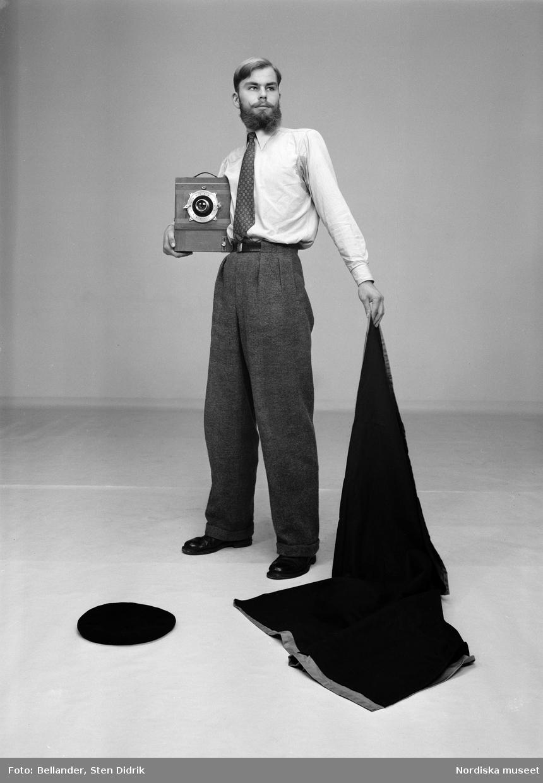 Fotograf Per Krafft håller kameraskynket som en slängkappa eller matadorskynke. På golvet ligger hans basker och i handen håller han storformatskameran.