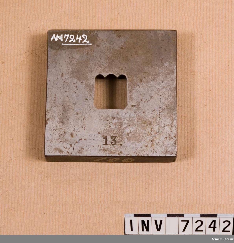 Samhörande nr är 1677-99, 1800-99, 2100-23. Utpressningsverktyg för fjäll nr 13. Den s.k. dynan eller hondelen. En fyrkantig platta med hål för fjäll nr 13. Genom urtaget för fjället pressas stansen.  På kanten målat med gul färg: 106. Gott skick.Originalet tillverkat av H. Müller i Stockholm.  Samhörande verktyg 7242-7243.