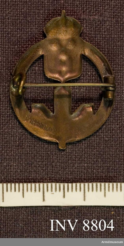 """CFB Fältpostmärke för ungdom. Bronsfärgat märke med upptill hemvärnets emblem och nedtill grönmålat tre grankvistar m ett ovanpå liggande U. Frånsidan är märkt """"Sporrong AB""""."""