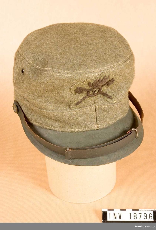 """Grupp C I. Ur uniform m/1915 för manskap, ingenjörstrupperna, Italien. Består av lägermössa, vapenrock, byxor, benlindor, krage och skodon. Käppi av grå-grönt kläde. På framsidan skärm av kakifärgat läder. På båda sidor finns hål för luftväxling. Foder av vitt tyg med """"54"""" på botten (storleksnummer). På båda sidorna svettrem av svart läder. Hakremmar av kakifärgat läder som knäppes till käppin med benknappar. På framsidan finns fastsydd kakifärgad klädesbit med broderade två yxor i kors och flammande bomb med nummer """"V"""" i mitten (femte """"Mineur"""" regementet). LITT  Handbuch der Uniformkunde, prof. Richard Knötel, Hamburg 1937, s 234, 235. Redan år 1908 provades khakifärgade uniformer i italienska armén. Under världskriget år 1915 infördes kakiuniform."""