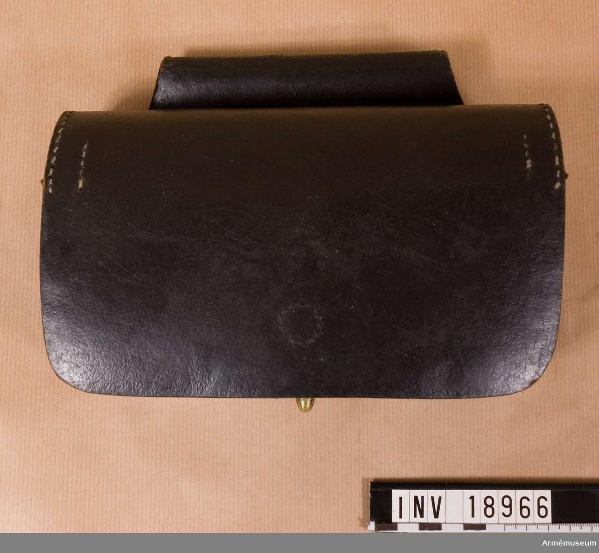 """Grupp C II. Av svart läder' Består av lock, som stängs med en rem med knapphål. På lockets baksida finns en stämpel: """"KG"""" (KungligaGardet). Därefter själva väskan, som har två skilda avdelningar för patroner och en särskild ficka, avrundad och med lock,  för kapslar. På väskans nedre del finns en mässingsknapp ooh på baksidan en ögla, b:120 mm, för livrem. Pappersetikett från Stockholms tygstation med text """"0-264"""". påskri6ffren """"0 - 264"""". LITT   Album: """"Svenska och Norska armeén"""". På bilden """"Kungl. Norske Garde Skarpskytter"""" bär soldaterna likadana patron- väskor.Enl kapten W Granberg."""