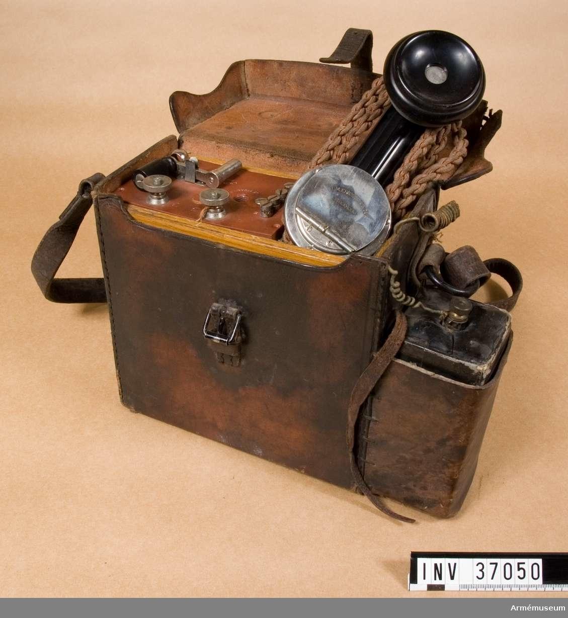Grupp H I.  En fälttelefon med vevinduktor, polariserad ringklocka och handmikrotelefon i läderetui.  Handmikrotelefonen är av L M Ericssons ryska, hopskjutbara typ.