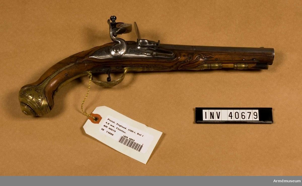 """Grupp E III. Pistol med flintlås ej avsett för militärbruk. Kammarstycket prytt med gravyr, märkt """"London"""". På vänstra sidan inslaget """"45"""", två kronstämplar och mellan dem """"M.G."""". Låset är prytt med gravyr. Beslag av mässing, cislerade. På kolvens vänstra sida ovanför kolvkappan inslaget """"45""""."""