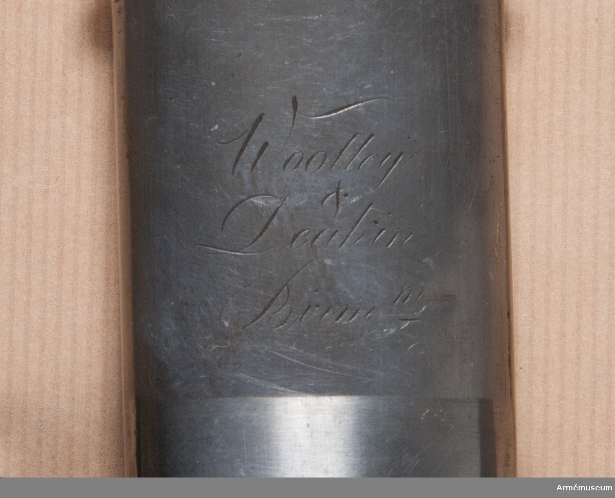 """Grupp D II. Baljan är helt av järn och har två rätt smala band för koppelringarna. På det övre av dessa band står på utsidan """"23 RB No 6"""". På baljans insida nära mynningen """"Wolley Deakin.  Birm"""".Pallaschen är en pallasch m/1790 för tunga engelska kavalleriet  och har ingått i det parti på 4000 sidovapen, som 1808 inköptes  i England för svenska arméns räkning. Pallascherna tilldelades  svenska kavalleriet och användes delvis till in på 1880-talet."""