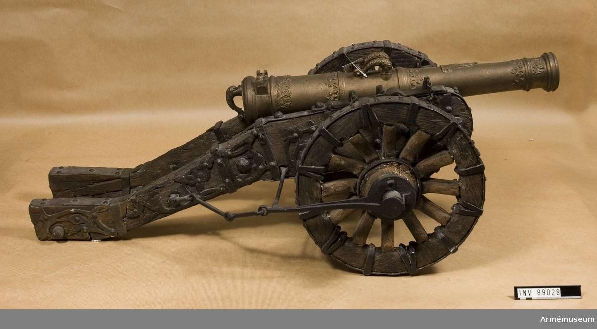 """Grupp F I. Modell av 18-pundig kanon. 1600 ca. Modellen består av eldrör, lavett och riktkil. Enligt uppgifter i kapten F A Spaks katalog 1888. """"Kanonen dåligt tillverkad, troligen gjord på 1800-talets mitt och möjligen avgjuten av en äkta pjäs. Enligt Spak från slutet av 15- eller början av 1600-talet, ursirad med flera prydnader och i lavett från samma tid. Skala 1/5. Kanonen är en gåva av konung Oscar II medan lavetten deponerats av livrustkammare. Dock syns såväl kanon som lavett från början ha varit avsedda för varandra."""""""