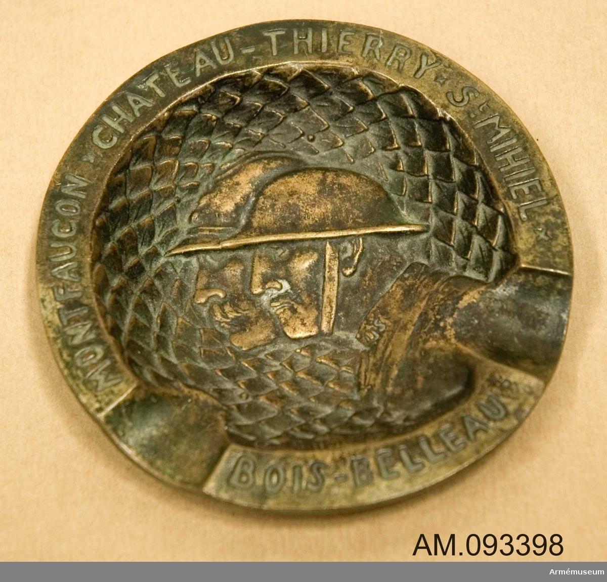 Runt askfat med fiskbensmönstrad botten prydd med två män i profil iförda uniform med hjälm. Runt kanten text, (se påförd text).