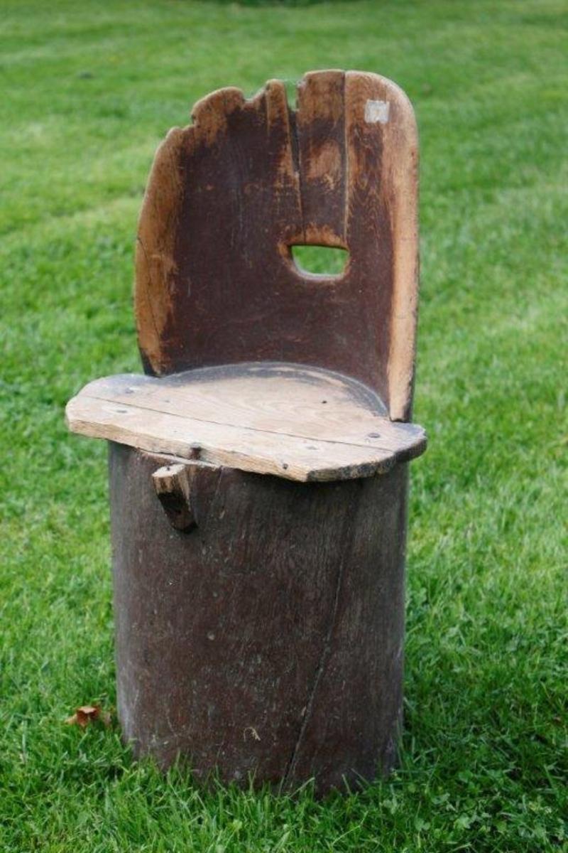"""Form: Sylinderform under setet. Ryggen forsattelse av stammen, buet overside, noen sprekker og hakk.D-forma hol i rygg. Tilnærma sirkulært sete, freme stykke flat av. Furu i sete. Laget av hel bjørk. M: """"Nr.42. Kubbestol. Gave fra Hans Hilton, Hvam, Nes""""."""
