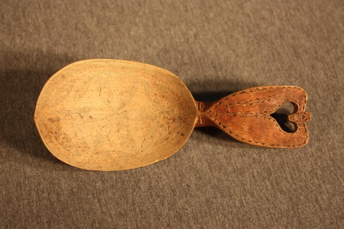 Skjoldforma skaft med gjennombrote hjarte trekantmønstra bord rundt skaftet i karveskurd. Geometrisk mønstra kolrosing på bladet.