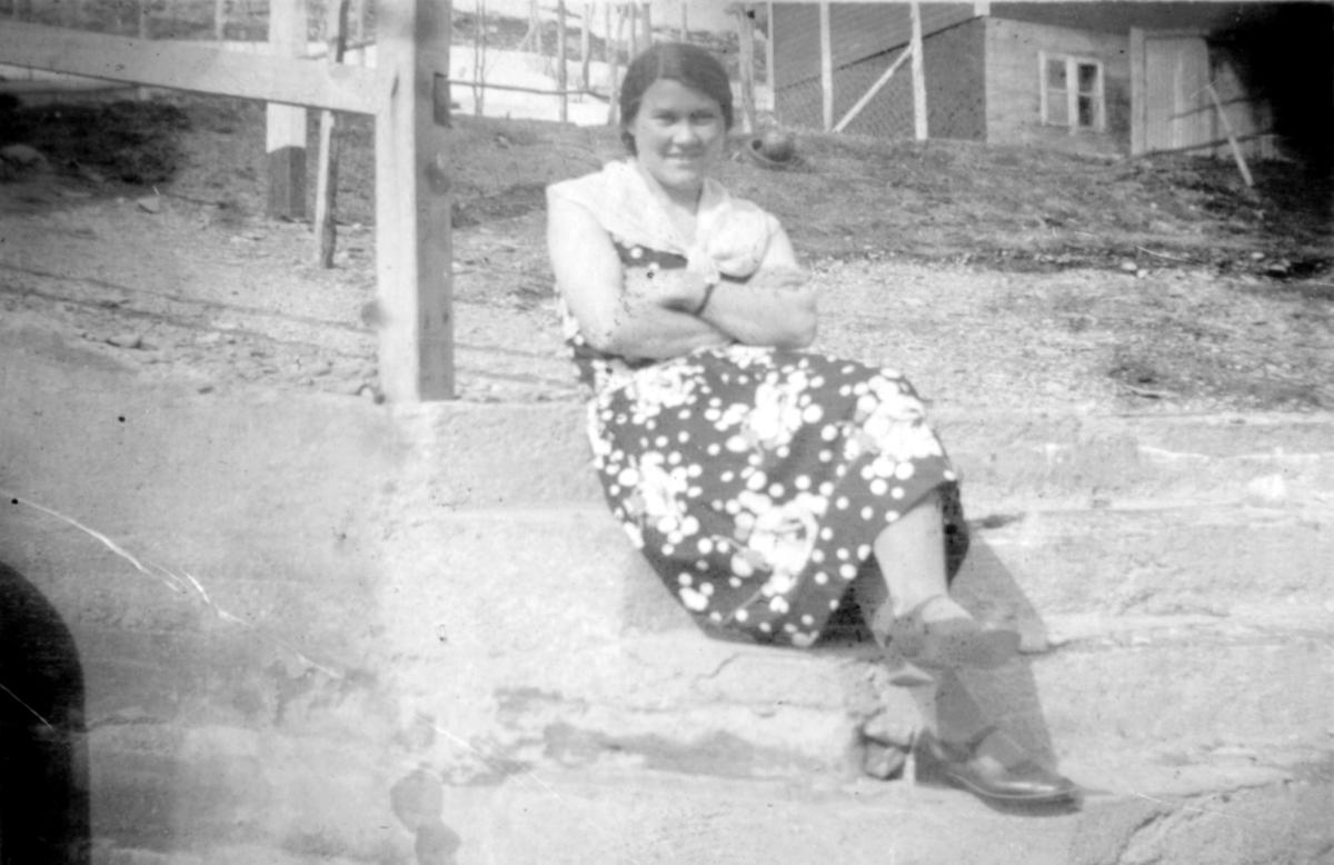 En kvinne sitter på bakken og et hus står i bakgrunnen. Sted og person er ukjent, men bildet kan være tatt i Kvalsund kommune en vårdag, før evakueringa.