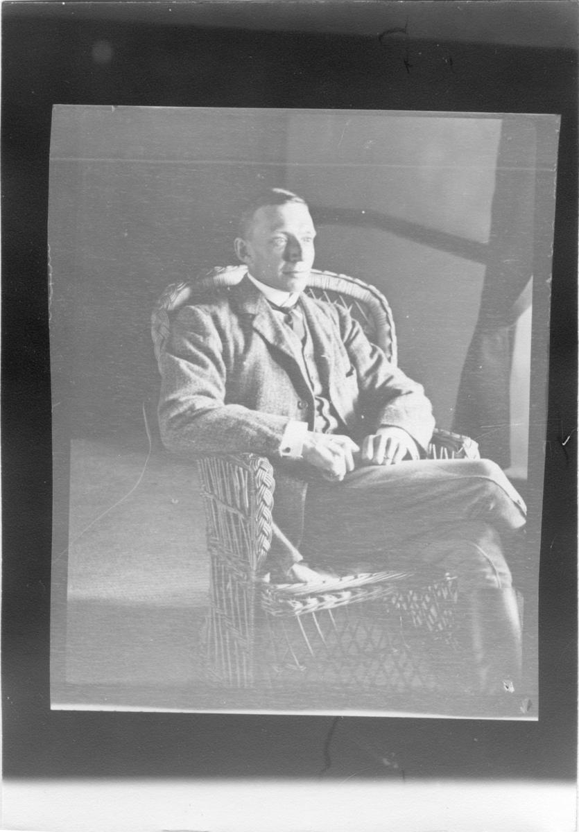 'Diverse fotografier från bl.a. dåvarande Nordrhodesia, nu Zambia, tagna av Konsul Magnus Leijer. ::  :: En man sittandes i en rottingfåtölj vid ett fönster. Fotograferad snett framifrån.'