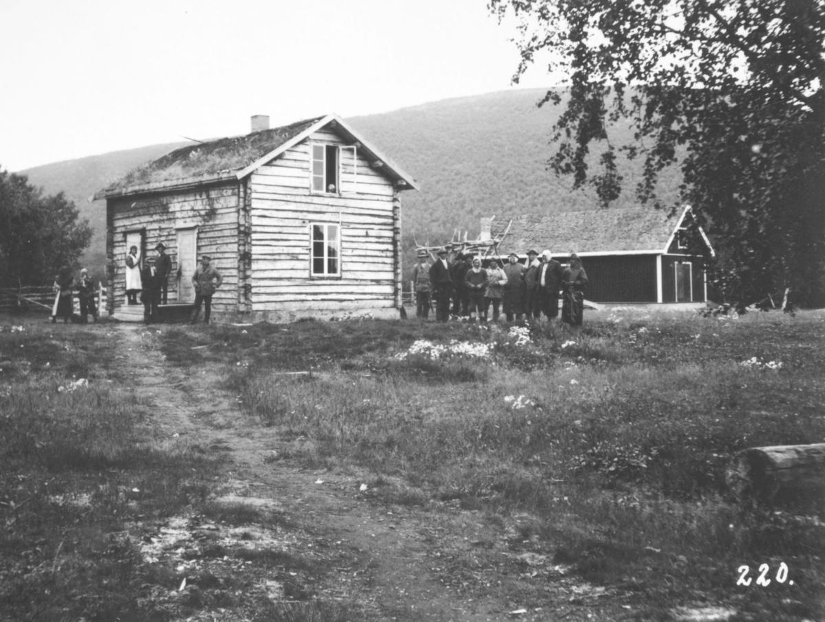 Jordbrukskomiteen på Stortinget foretok en reise til Finnmark i 1935. Kleppe var med og ga bildene sine fra denne turen til fylkesmann Gabrielsen etter krigen. Her har Kleppe fotografert en gruppe mennesker utenfor hos bureiser Ole A Rasmus, Port. Vi ser våningshus og uthus.
