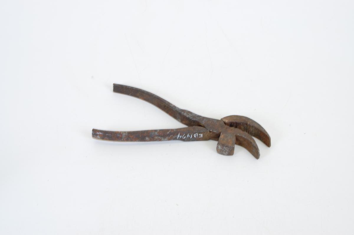 Form: Innbuede håndt., Kjeft form. som et bøyd nebb. Innsid. griperiller, u. kjeft: en rektang. hammer. Tangen er brukt til å holde såle og overlær sammen når en skal sy.
