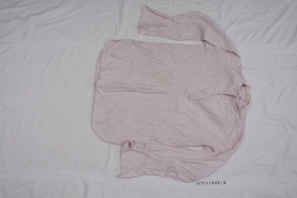 Skjorte uten krage. Hvit med lilla rutemønster. Kun åpning i øvre del av skjorte, lukkes med to knapper.