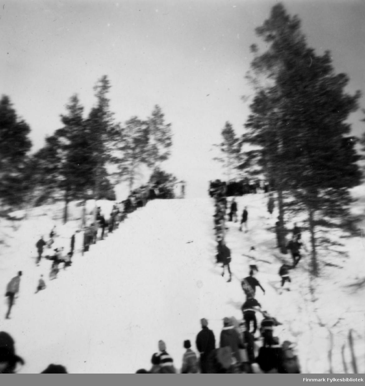 Hopprenn i Karasjok. En del tilskuere står i bakken og nede på sletta.